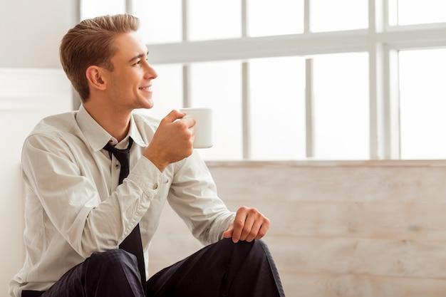 男は笑みを浮かべて、部屋に座っている間カップを持っています。