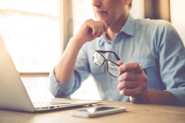 ハンサムな実業家のラップトップを使用して彼の眼鏡を保持