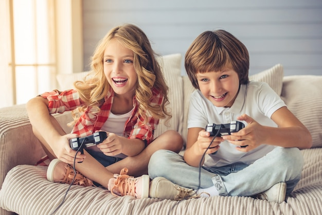 Хорошенькая девочка и мальчик играют в игровую консоль.