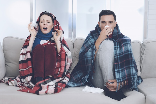 若い病気のカップルは敷物とソファの上に座っています。