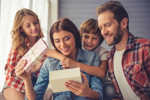 Любящие дети и муж дарят подарок.