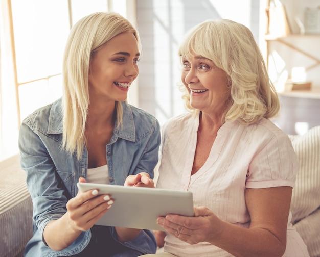 Старая женщина и молодая девушка используют цифровой планшет.