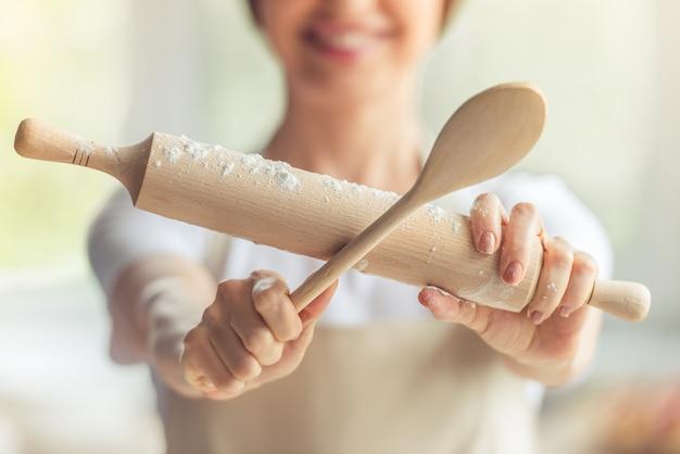 Обрезанное изображение женщины, держащей деревянной ложкой.
