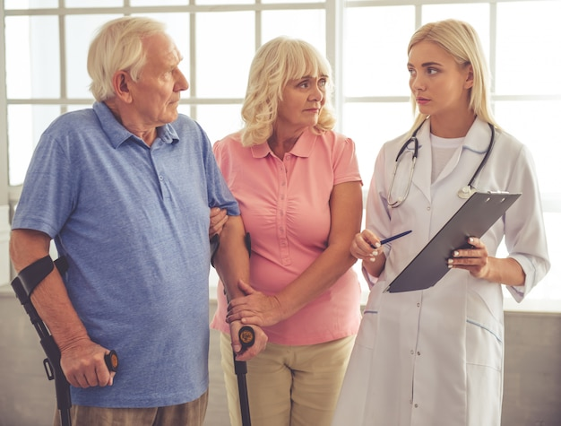 Красивая молодая женщина-врач разговаривает со старой парой.
