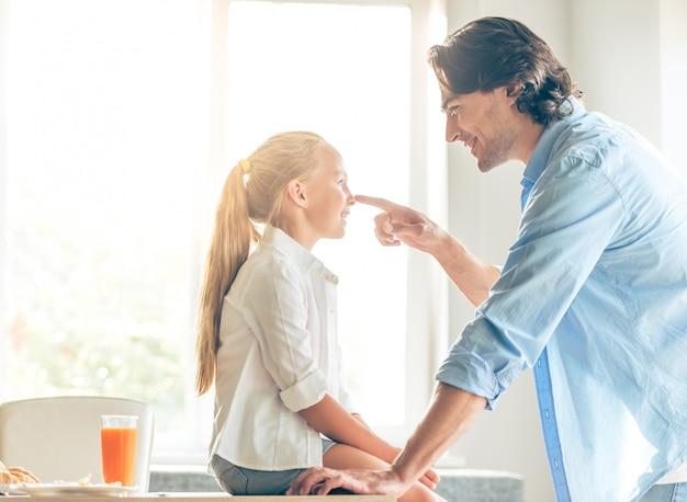 かわいい女の子と彼女のハンサムな父親は話しています。