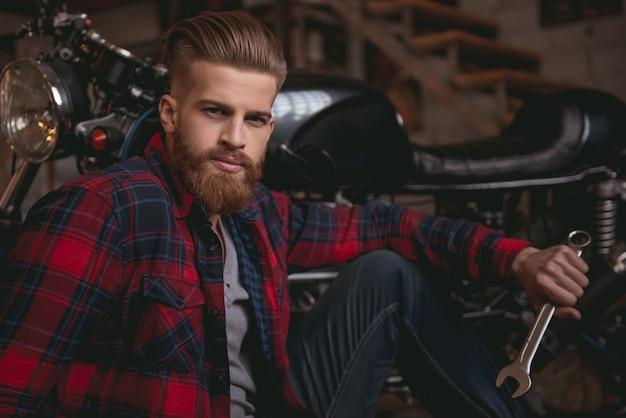Бородатый мужчина в повседневной одежде держит гаечный ключ.