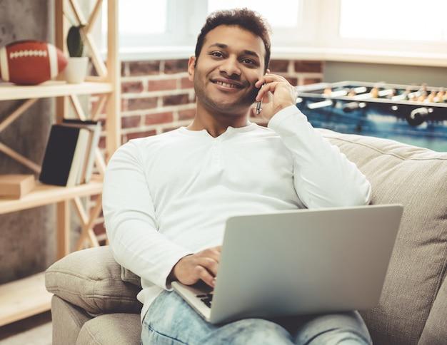 魅力的なアフロアメリカンの男はラップトップを使用しています。