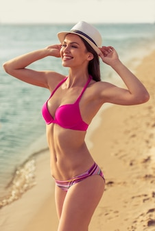 Красивая девушка в розовом купальнике ставит шляпу на голову.