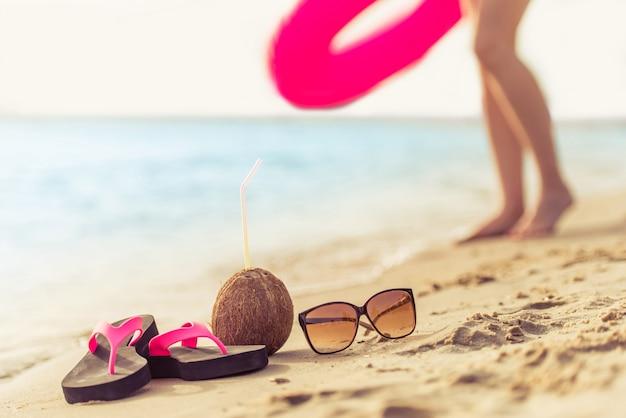 Шлепанцы, кокосовый коктейль и солнцезащитные очки находятся на пляже.