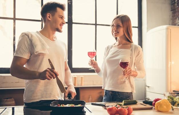 ハンサムな男は笑みを浮かべて、台所で料理をしています。