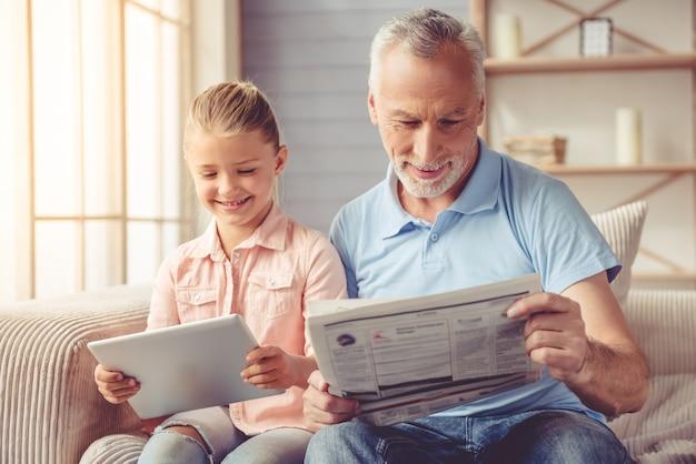 Милая маленькая девочка и ее красивый дедушка улыбаются.