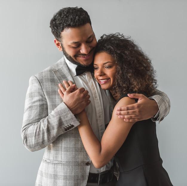 フォーマルな服装で美しいアフロアメリカンのカップルはハグしています。