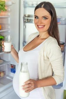Красивая беременная женщина держит бутылку молока.