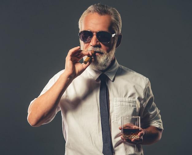 古典的なシャツでハンサムなひげを生やした成熟した実業家。