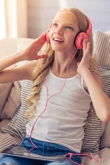 ヘッドフォンで金髪の十代の少女は音楽を聴いています。
