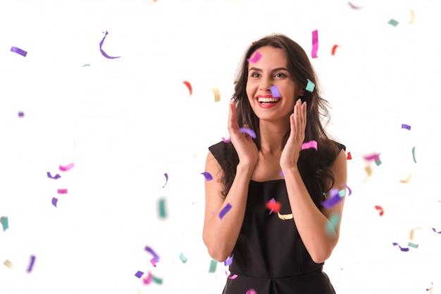 黒のカクテルドレスで美しいエレガントな女の子は笑っています。