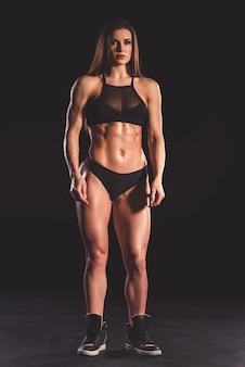 Полная длина портрет красивой сильной мышечной женщины.
