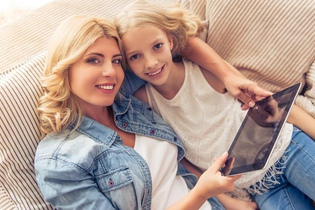 女性と彼女の十代の娘はタブレットを使用して。