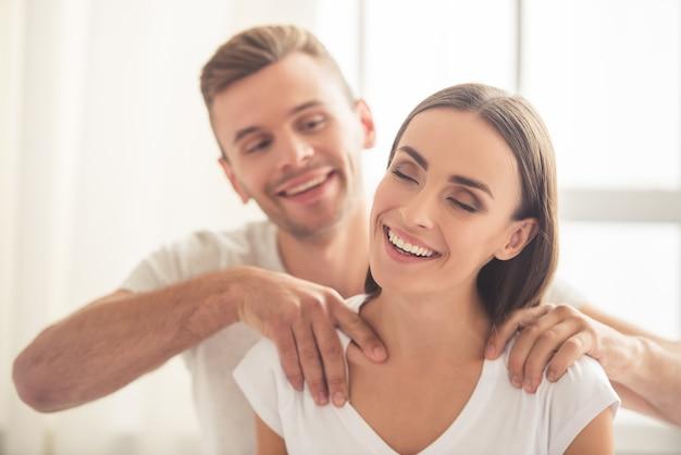 若い男は彼の美しいガールフレンドマッサージをしています。