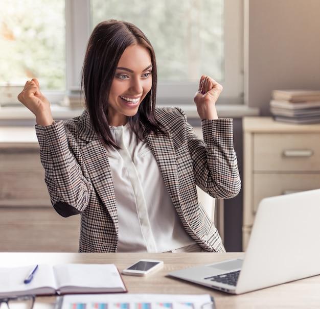 フォーマルな服装の女性実業家はノートパソコンを見ています。