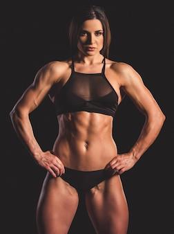 Красивая сильная мускулистая женщина в черном нижнем белье.