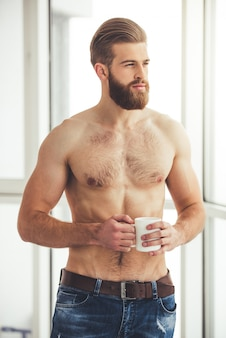 裸の胴体を持つハンサムなひげを生やした男がカップを持っています。