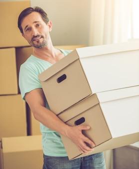 カジュアルな服装でひげを生やした男は箱を運んでいます。