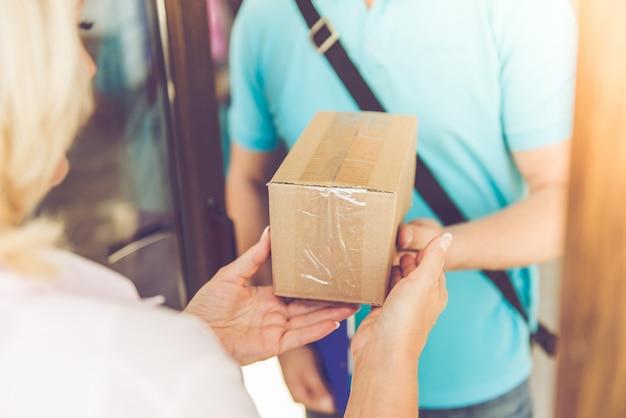 Женщина получает доставку от красивого работника.
