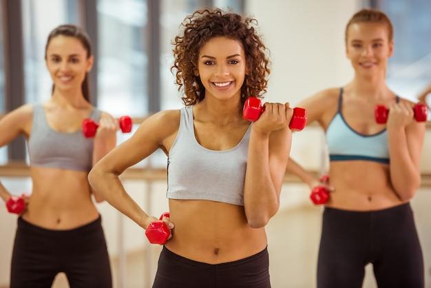 Привлекательные девушки улыбаются во время тренировки с гантелями.