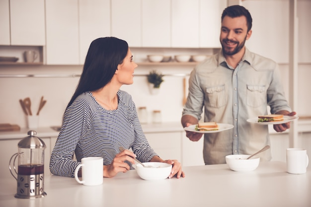 美しいカップルはサンドイッチを食べて、話して、笑っています。