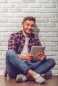 カジュアルな服装と帽子の少年はデジタルタブレットを使用しています。