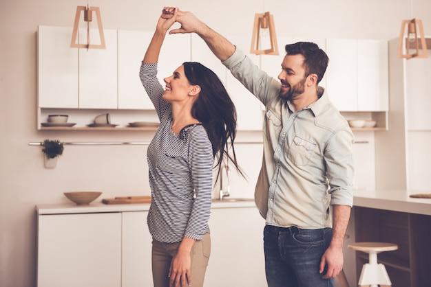 美しいカップルが自宅の台所で踊りながら笑っています。