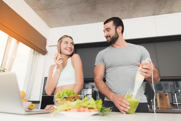 若いカップルは朝食を準備しています。