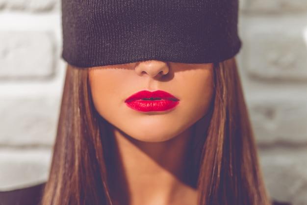 彼女の目に黒い帽子を持つスタイリッシュな若い女の子の肖像画。