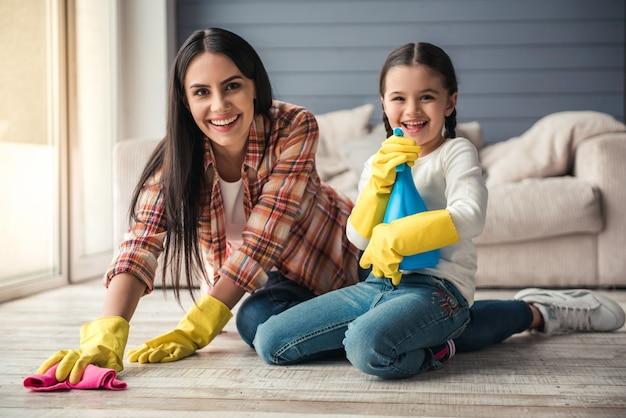 女性と彼女の娘は床を掃除しながら笑っています。