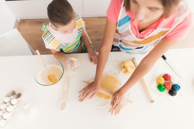 女の子と母親は台所で料理をしています。