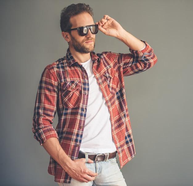 カジュアルな服装とサングラスでスタイリッシュな若い男。