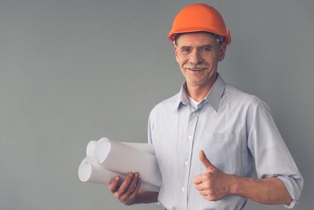 保護用のヘルメットでハンサムな成熟した建築家。