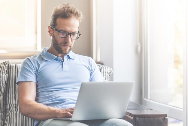 Бизнесмен использует ноутбук и улыбается.