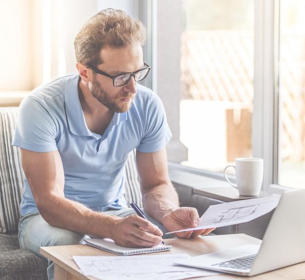 ビジネスマンは自宅のソファに座りながらノートを作っています。