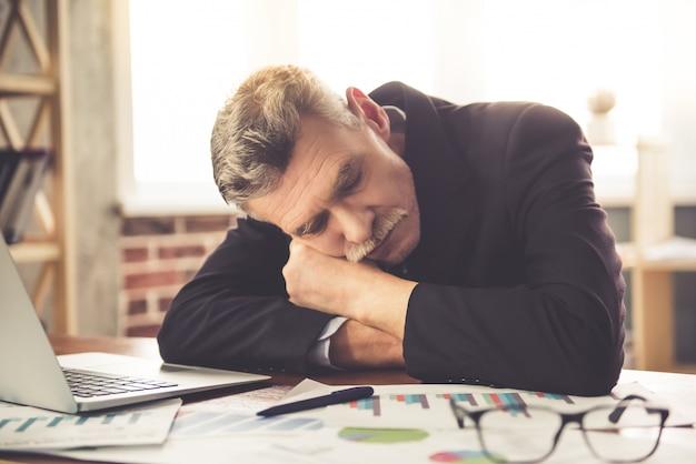 古典的な服で疲れたビジネスマンはテーブルの上で昼寝しています。