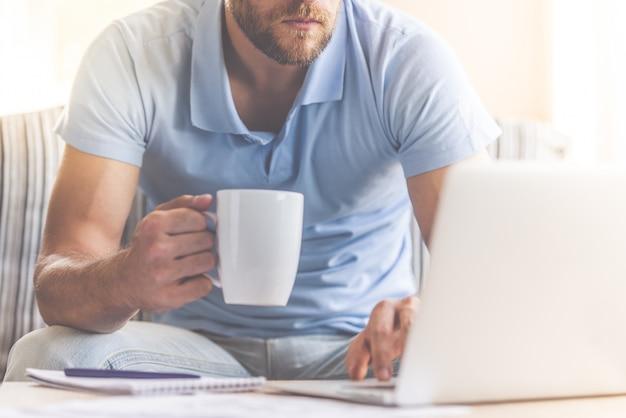 ビジネスマンは自宅で仕事をしながら一杯のコーヒーを保持しています。