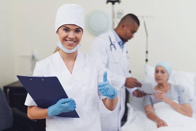 Медсестра позирует на фоне пациента.