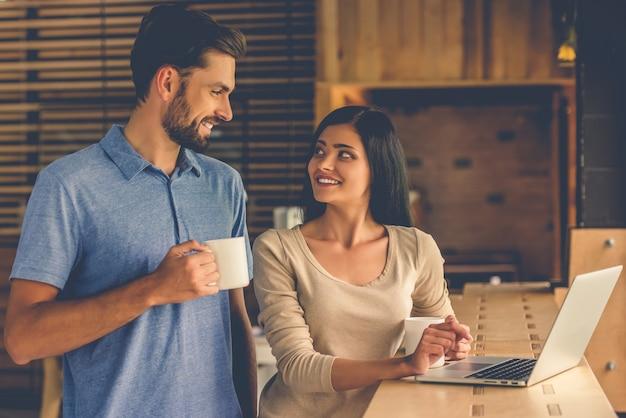 美しいデザイナーのカップルはラップトップを使用しています。