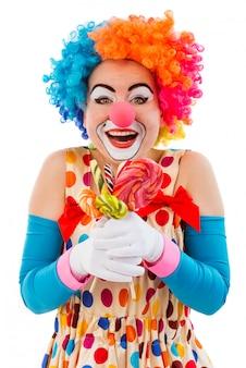キャンディーを保持しているカラフルなかつらで面白い遊び心のある女性ピエロ。