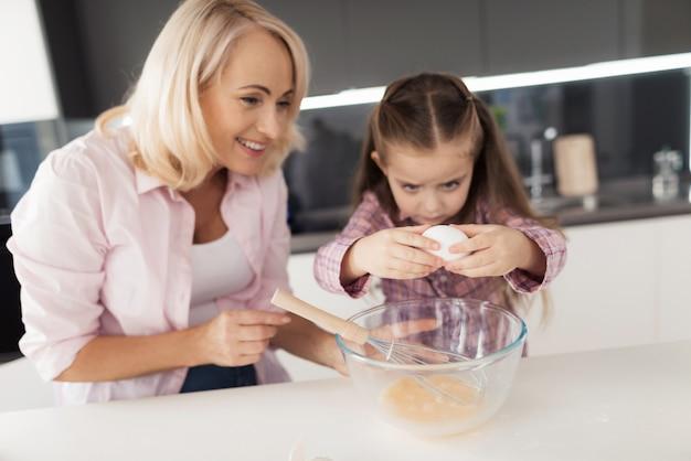 祖母の笑顔女の子は卵をボウルに分割します。