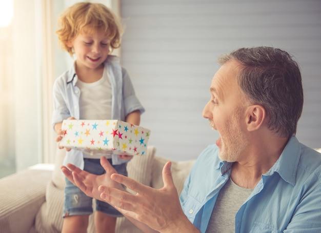 かわいい男の子は彼のおじいちゃんに贈り物をすると笑顔です。