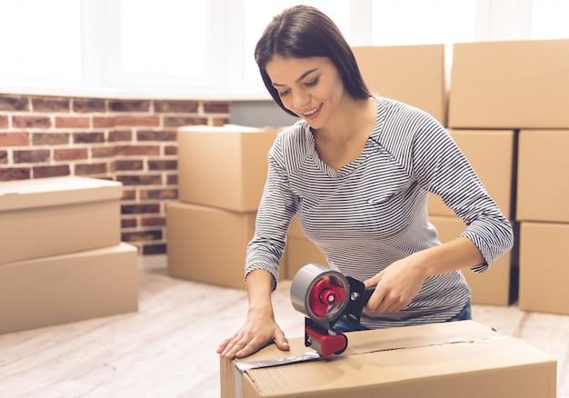 Девушка упаковывает движущуюся коробку с помощью клейкой ленты.