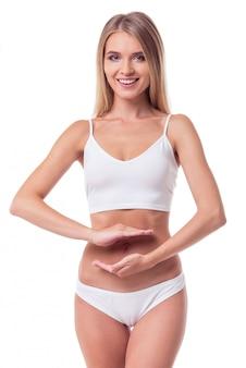 白いランジェリーの女の子は彼女の胃の近くに手を繋いでいます。ダイエットの概念