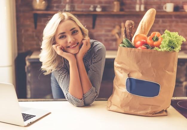美しい少女は紙の買い物袋の近くのテーブルに寄りかかっています。